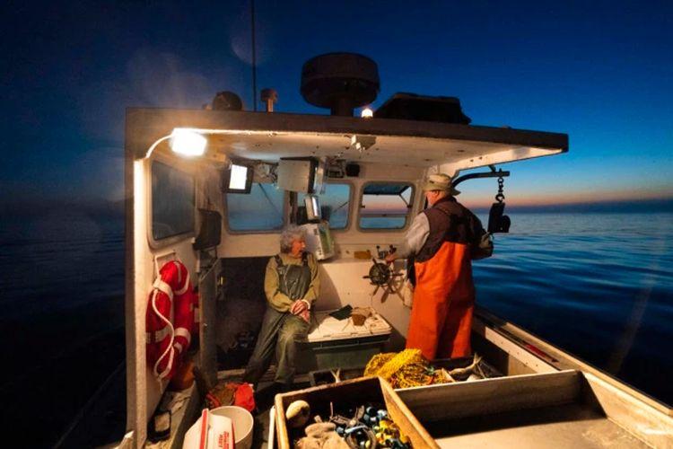 Virginia Oliver (kiri), mengobrol dengan putranya Max Oliver saat berangkat ke laut untuk menangkap lobster saat fajar di Rockland, Maine, Selasa, 31 Agustus 2021. Virginia Oliver (101 tahun), nelayan lobster tertua di negara bagian itu.