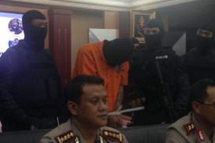 A (39), tersangka pembunuh bocah dalam kardus di Kalideres, Jakarta Barat, PNF (9), menunduk sepanjang rilis pengungkapan kasus tersebut di Mapolda Metro Jaya, Sabtu (10/10/2015).