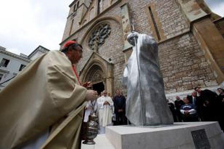 Kardinal Bosnia Vinko Puljic meresmikan patung Paus Yohanes Paulus II di depan katedral Hati Yesus, Sarajevo, Rabu (30/4/2014). Dukungan Paus Yohanes Paulus II kepada warga Bosnia selama perang 1992-1995 dan dorongannya untuk menghancurkan sekat-sekat etnis dan agama membuatnya sangat populer di mata warga Bosnia, apapun agama yang mereka peluk.