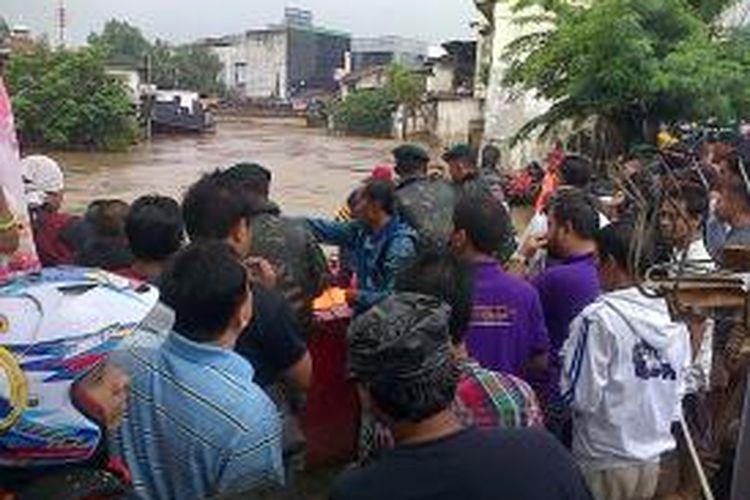 Warga berkerumun melihat aksi tim SAR dan pasukan Kostrad yang mengevakuasi korban banjir Sungai Ciliwung di Kampung Pulo, Jakarta Timur, Selasa (21/1/2014).