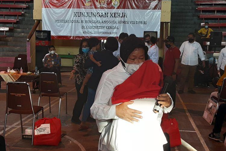 Menteri Sosial, Tri Rismaharini, saat dipeluk anak yatim yang menangis. KOMPAS.COM/SLAMET PRIYATIN
