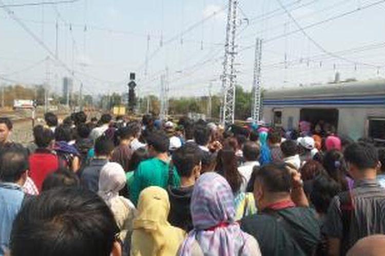 Para penumpang rangkaian KRL commuter line relasi Bogor-Tanah Abang-Jatinegara saat diminta untuk berpindah ke rangkaian KRL, di Stasiun Manggarai, Rabu (30/9/2015). Penumpang diminta untuk berpindah kereta karena adanya gangguan wesel di jalur lima Stasiun Manggarai.