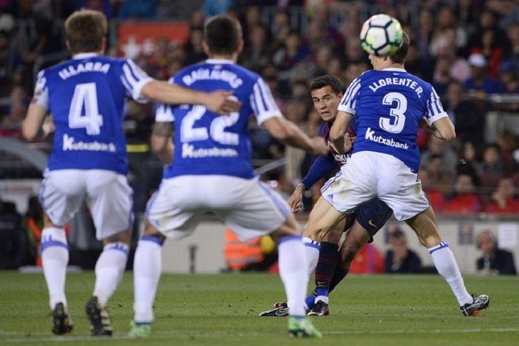Tendangan pemain Barcelona, Philippe Coutinho, melewati hadangan bek Real Sociedad pada pertandingan La Liga di Camp Nou, 20 Mei 2018.