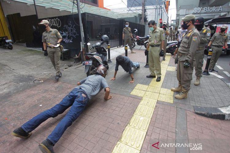 Petugas gabungan memberikan hukuman push up kepada warga yang tidak memakai masker saat razia penerapan aturan Pembatasan Sosial Berskala Besar (PSBB) di Kawasan Jalan Fatmawati, Jakarta, Selasa (28/4/2020).