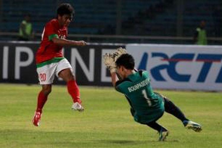 Pemain Indonesia, Ilham Udin Armaiyn melancarkan serangan ke penjaga gawang Laos, Bounpaseuth Niphavong pada kualifikasi Piala Asia U-19 di Stadion Utama Gelora Bung Karno, Jakarta, Selasa (8/10/2013). Indonesia unggul 4-0.