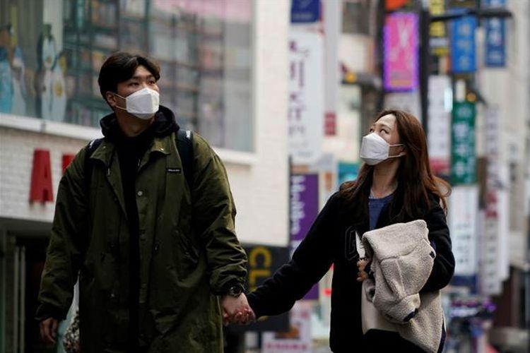 Sepasang warga Korsel nampak bergandengan tangan di kota Seoul. Hari ini (6/5/2020) Pemerintah Korsel mulai melonggarkan kebijakan social distancing dan warga mulai berkativitas secara normal.