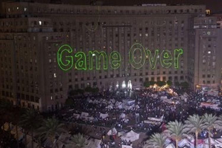 Para pengunjuk rasa anti-Presiden Mursi menggunakan sinar laser untuk mengungkapkan isi hati mereka. Salah satu sinar laser yang dipancarkan ke sebuah gedung bertuliskan