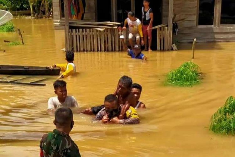 Bhabinkamtibmas Pangkalan Kasai Aipda Ikhsan Lutfi menggendong kakek Paimin (70) mengarungi banjir yang melanda Desa Pangkalan Kasai, Kecamatan Siberida, Kabupaten Inhu, Riau, Rabu (11/11/2020).