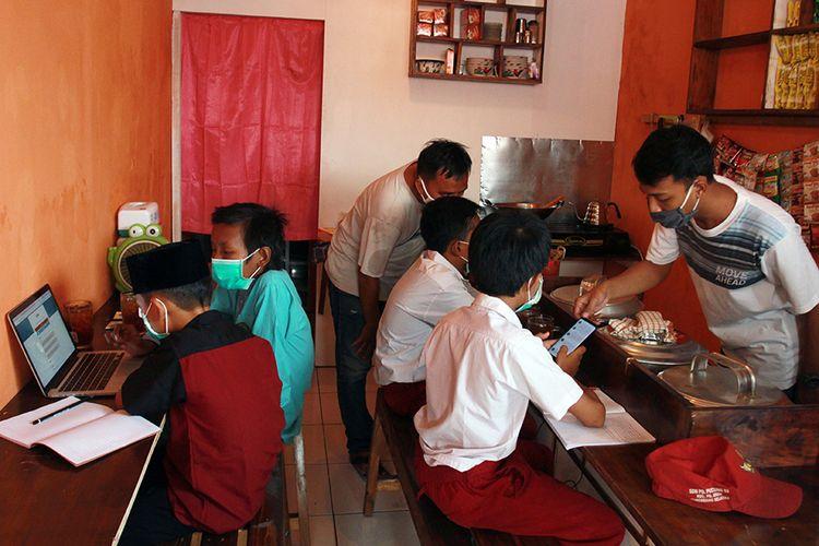 Sejumlah pelajar sekolah dasar (SD) mengikuti pembelajaran jarak jauh dengan memanfaatkan jaringan internet gratis yang disediakan sebuah warung kopi di Jombang, Tangerang Selatan, Banten, Rabu (29/7/2020). Penyediaan jaringan internet gratis yang diberikan pemilik warung kopi tersebut merupakan bentuk kepedulian terhadap dunia pendidikan di tengah pandemi COVID-19.