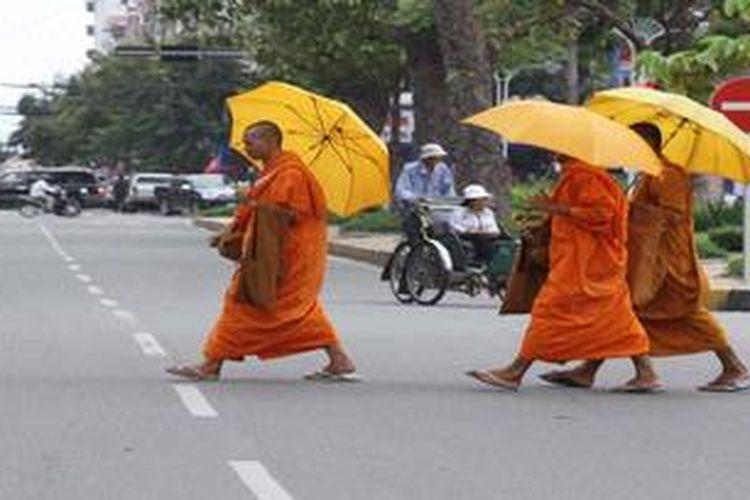 Tiga orang bhiksu menyeberangi salah satu jalan protokol di Kota Phnom Penh, Kamboja, Jumat (16/11/2012). Penduduk beraktivitas normal di tengah pelaksanaan Konferensi Tingkat Tinggi ASEAN ke-21 di kota tersebut.