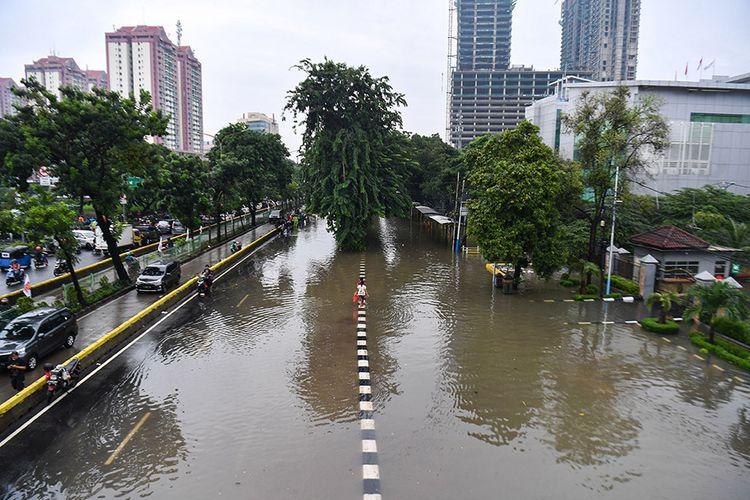 Warga berjalan melintasi banjir di Jalan Letjen Suprapto, Jakarta Pusat, Sabtu (8/2/2020). Hujan deras yang mengguyur Jakarta sejak Sabtu (8/2) dini hari membuat sejumlah kawasan di Ibu Kota terendam banjir.