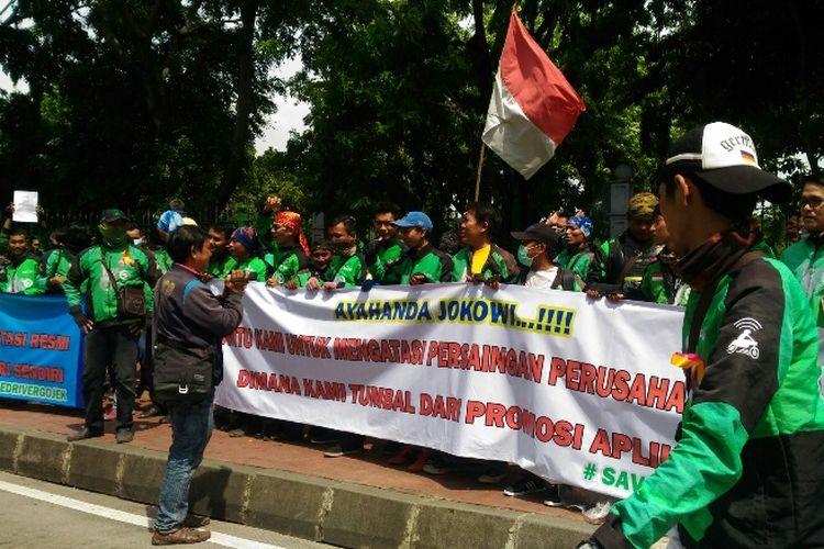 Massa ojek online membentangkan spanduk di Lapangan IRTI sebelum long march ke Kemenhub dan Istana Negara, Kamis (23/11/2017).