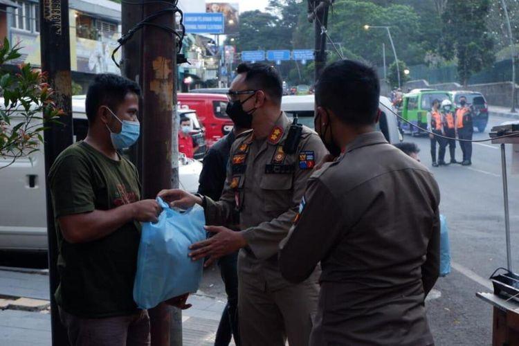 Kepala Satpol PP Kota Bogor Agustian Syach saat memberikan bantuan sembako kepada salah satu pedagang yang terdampak PPKM darurat.