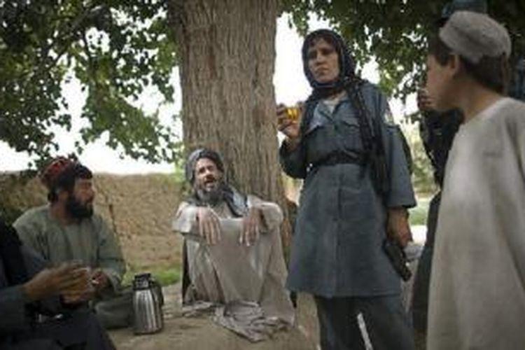 Seorang polwan Afganistan minum teh bersama penduduk desa Samir Kalacha tahun 2010.