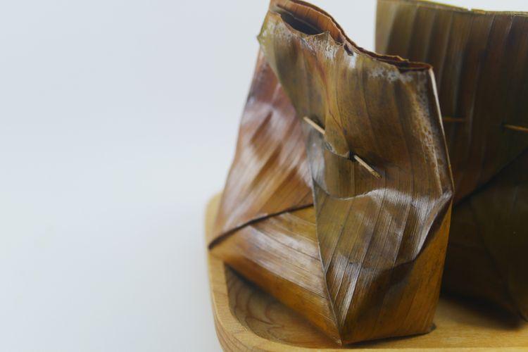 Ilustrasi tum ayam dibungkus daun pisang.