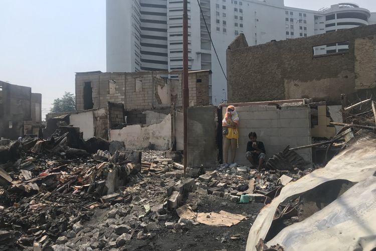 Dua orang warga, Senin (13/5/2019), mengamati puing-puing bekas rumah mereka  yang terbakar di Kampung Bandan, Tanjung Priok, Jakarta Utara. Api melalap sejumlah rumah di RT 011, 012, dan 013 RW 005 di kawasan itu pada Sabtu lalu.