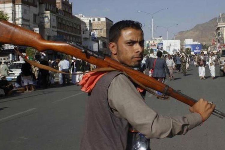 Pemberontak Houthi Syiah membawa senjata saat ia bergabung dalam aksi protes terhadap serangan udara Saudi Arabia, di Sanaa, Yaman, 1 April 2015.