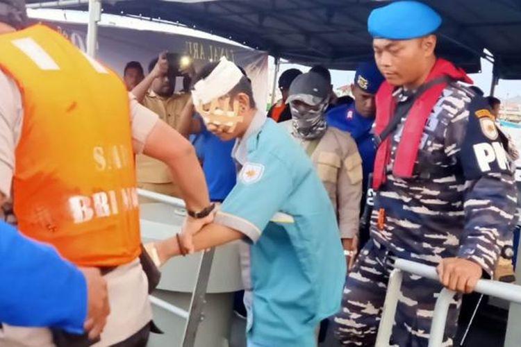 Seorang ABK KM Mina Sejati dengan kepala diperban diturunkan dari KRI Teluk Lada ke Speedboat untuk diantar ke Pelabuhan Dobo,Kepulauan Aru,  Selasa (20/8/2019)