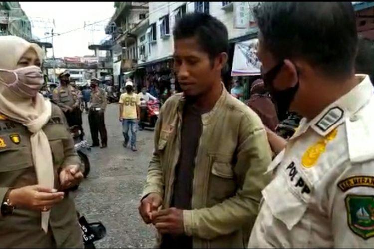 Tangkapan layar video saat petugas mendapati seorang pria yang tak menggunakan masker meminta hukuman membaca surah Al-Fatihah di Kabupaten Kepulauan Meranti, Riau, Rabu (15/9/2020).
