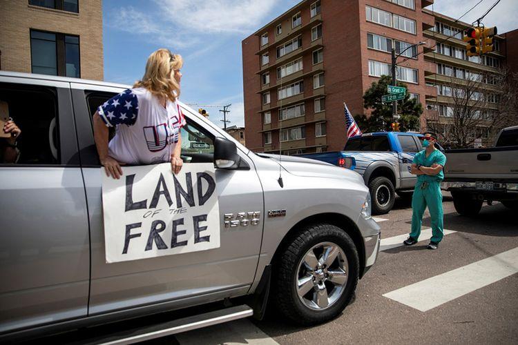 Petugas kesehatan berdiri di jalan sebagai protes-kontra terhadap ratusan warga yang berkumpul di State Capitol menuntut perintah tinggal di rumah dihentikan, di Denver, Colorado, Amerika Serikat, Minggu (19/4/2020). Berdasarkan data Johns Hopkins University, hingga Selasa (21/4/2020), AS masih menjadi negara dengan kasus Covid-19 tertinggi dunia mencapai 787.794 dengan korban meninggal 42.362.