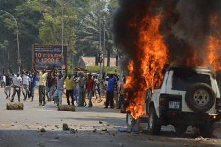 Warga Republik Afrika Tengah bersorak setelah melempari dan membakar mobil yang membawa keluarga mantan pemimpin Seleka di ibu kota Bangui. Gambar diambil pada 13 Januari 2014.
