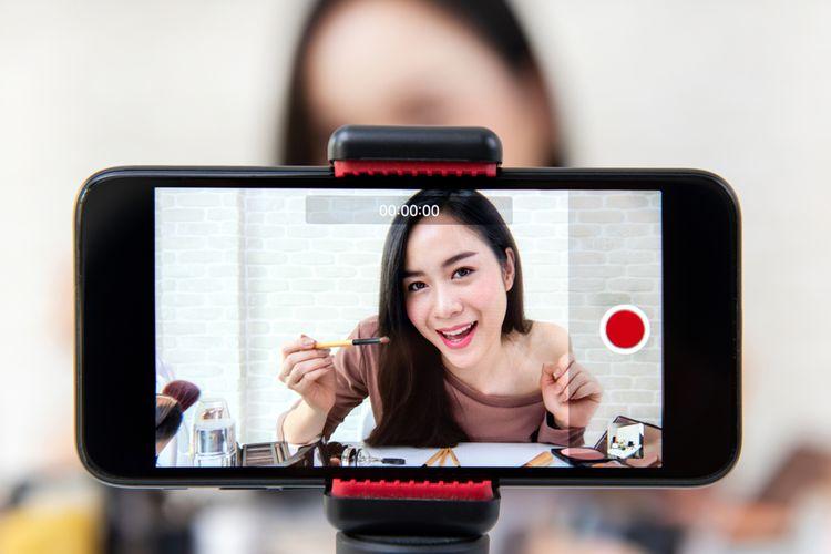 Wanita cantik yang berprofesi sebagai beauty vlogger sedang merekam aktivitasnya yang menjelaskan tutorial makeup.