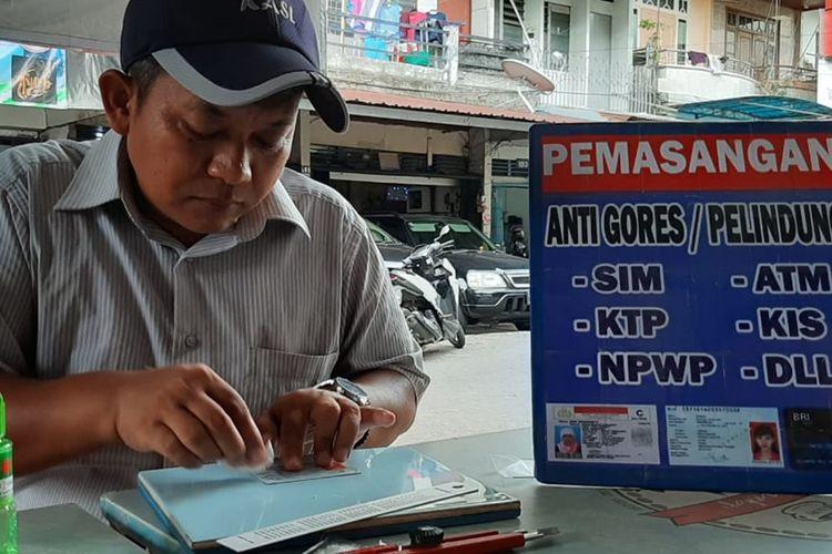 Suherman tengah memperbaiki KTP salah satu warga di Warung Kopi Asiang, Pontianak, Kalimantan Barat, Rabu (30/10/2019).