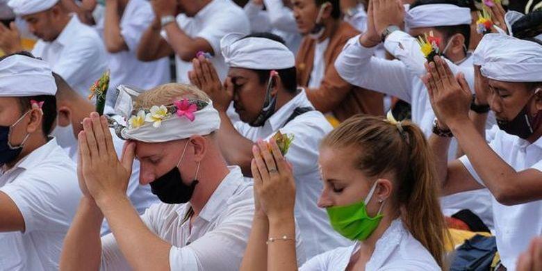 Dua warga negara Inggris mengikuti persembahyangan bersama dalam upacara Pamahayu Jagat di Pura Besakih, Karangasem, Bali, Minggu (5/7/2020)