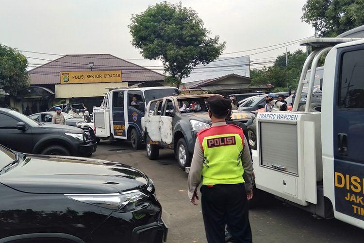 Petugas menderek dua mobil yang terbakar, dua mobil dalam kondisi pecah kaca dan satu bus operasional di Mapolsek Ciracas,  Sabtu (29/9/2020)