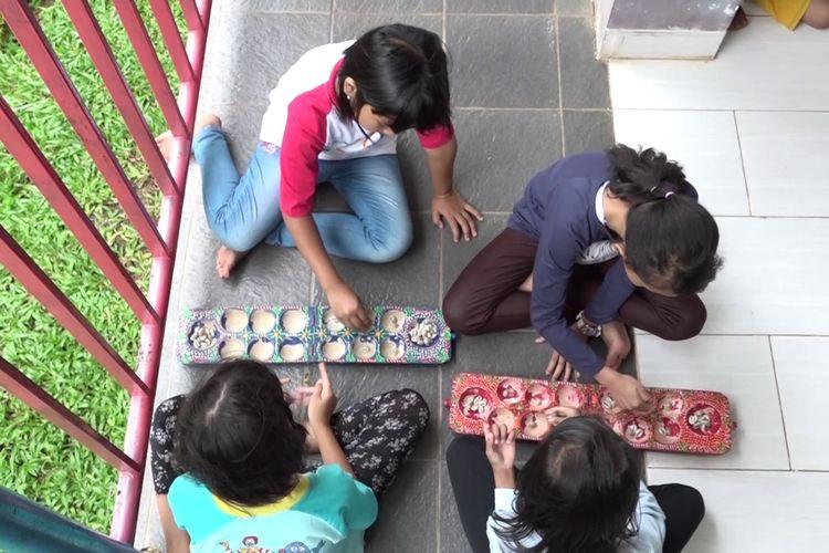 Ilustrasi anak-anak bermain congklak, permainan tradisional Indonesia.