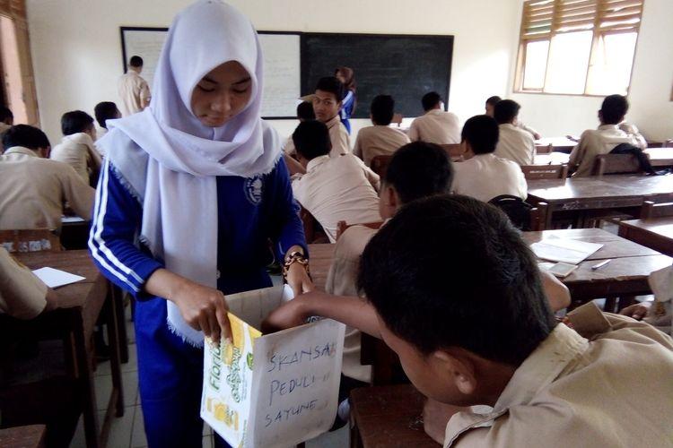 Salah seorang siswa menyisihkan uang sakunya untuk membantu korban banjir Sayung saat penggalangan dana yang dilakukan  oleh OSIS SMK Negeri Sayung,  Jumat (17/2/2017) pagi.