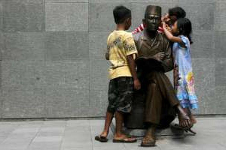Sejumlah anak-anak bermain dan mengamati detil patung baru Proklamator Ir Soekarno yang dipasang di situs Penjara Banceuy, Bandung, Jawa Barat, Minggu (10/5/2015).