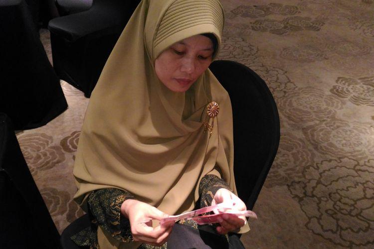 Seorang guru SLB Negeri Bontang Anissa Alhaqqoh Darwis tengah memperagakan cara mengajarkan membedakan uang pecahan Rp100.000 pada anak tunanetra. Uang cetakan baru dinilai sulit untuk dibedakan dan menghambat para tunanetra bisa mengenali pecahan uang tersebut.