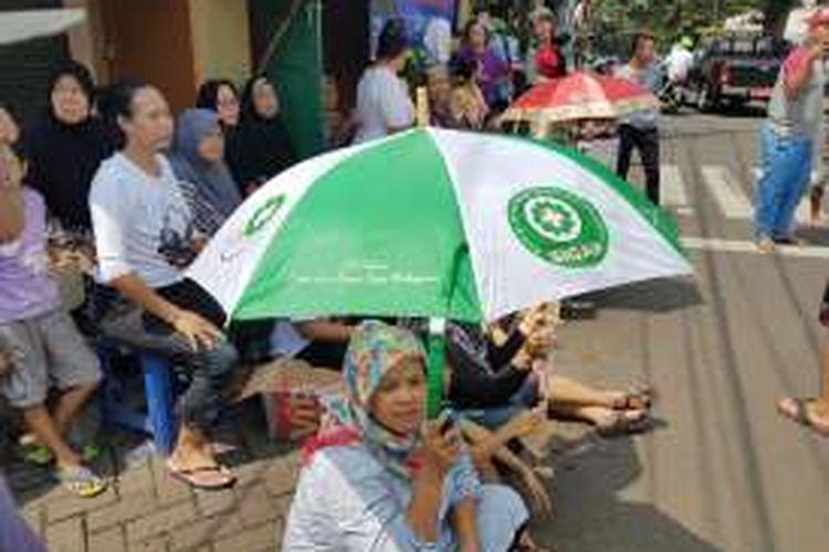 Warga Jalan Lauser mendengarkan pengunguman penundaan SP-2 di depan pintu masuk permukimannya di RT 08/08, Gunung, Kebayoran Baru, Jakarta Selatan, Senin (9/5/2016).