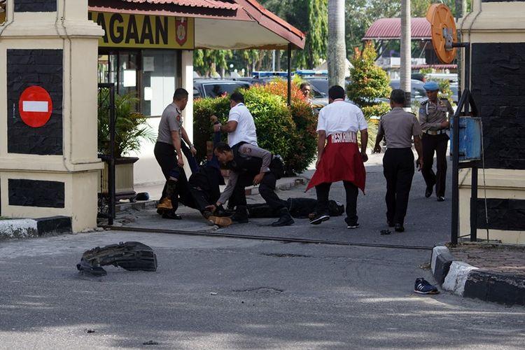 Petugas kepolisian mengevakuasi dua jenazah pelaku penyerangan di jalan pintu masuk Polda Riau di Pekanbaru, Riau, Jumat (16/5). Sejumlah pria menggunakan mobil minibus mencoba menerobos dan melakukan penyerangan ke Polda Riau pada sekitar pukul 09.00 Wib.