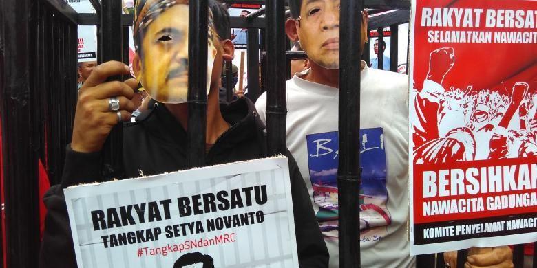Massa bertopeng Setya Novanto dan Riza Chalid dipenjara di depan Gedung KPK, Jakarta, Selasa (15/12/2015). Aksi tersebut mendesak aparat penegak hukum menangkap Riza dan Novanto.