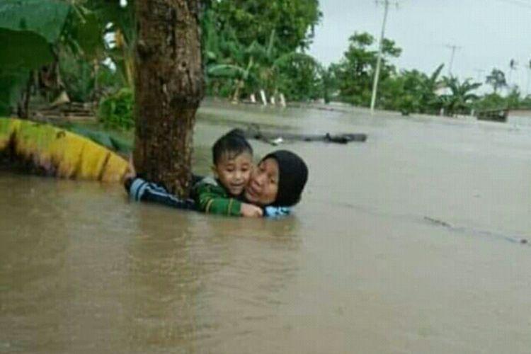 Nurjannah Djalil (70) saat menyelamatkan cucunya dengan berpegang pada pohon saat banjir bandang melanda Kabupaten Gowa, Sulawesi Selatan, Selasa (22/1/2019).