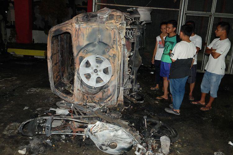 Warga melihat bangkai mobil yang rusak dampak kerusuhan di Lapas Narkotika Kelas III Langkat, di Langkat, Sumatera Utara, Kamis (16/5/2019). Akibat peristiwa kerusuhan yang dilakukan para narapidana di Lapas tersebut mengakibatkan tiga mobil dan dua sepeda motor petugas rusak terbakar dan ratusan napi melarikan diri.