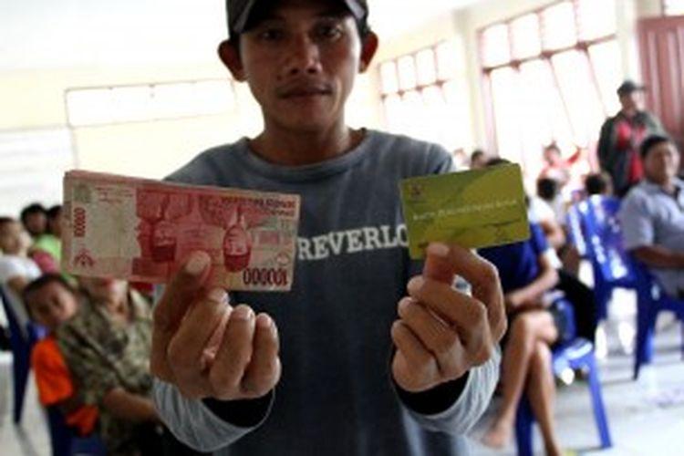 Seorang penerima dana BLSM di Manado menunjukkan Kartu Perlindungan Sosial dan dana yang diterimanya.