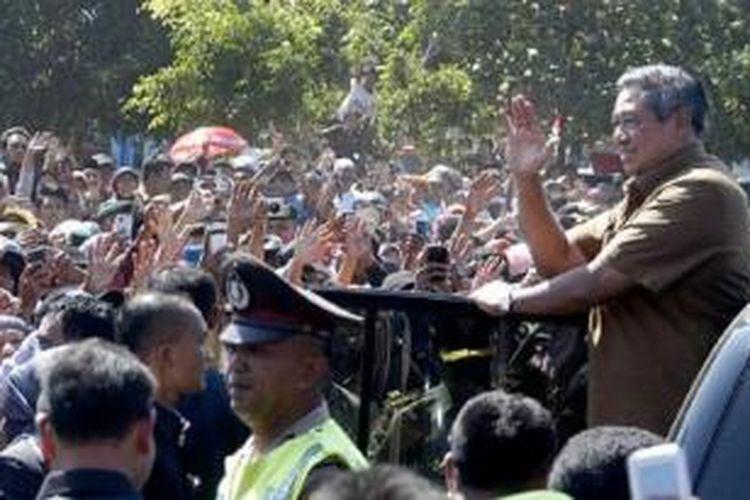 Presiden Susilo Bambang Yudhoyono melambaikan tangan kepada warga saat meninggalkan Tempat Pelelangan Ikan Puger, Jember, Jawa Timur, Rabu (31/7/2013). Dalam kesempatan itu, Presiden berdialog dan mendengarkan keluhan para nelayan Puger terkait pendangkalan kawasan muara Puger sehingga perahu tidak bisa merapat ke dermaga.