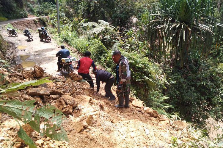 Warga setempat yang mengendarai sepeda motor terpaksa menerobos material longsor agar tidak terjebak di tengah hutan tanpa sinyal
