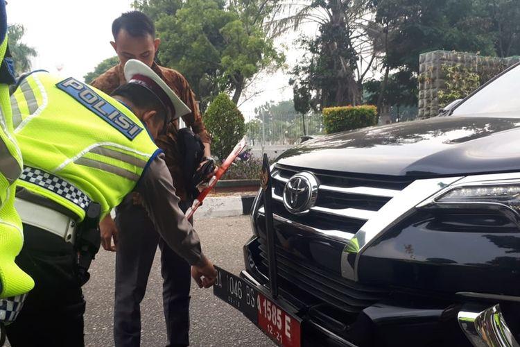 Petugas Ditlantas Polda Riau saat menilang mobil dinas anggota dewan Sumbar, yang menggunakan pelat palsu.