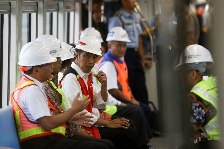 Presiden Joko Widodo (ketiga kiri) didampingi Menteri Perhubungan (Menhub) Budi Karya Sumadi (kedua kiri) serta Menteri Kabinet Kerja saat berada di dalam gerbong Light Rail Transit (LRT) atau kereta ringan saat meninjau pengoperasian LRT di Palembang, Sumatera Selatan, Jumat (13/7). Presiden Joko Widodo mengatakan LRT Palembang merupakan LRT pertama yang beroperasi di Indonesia.