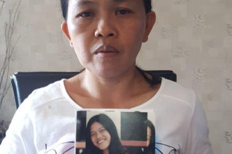 Seska Sumilat dengan foto anaknya Gabriella yang hilang di desa Jono Oge, Sigi, tahun lalu.