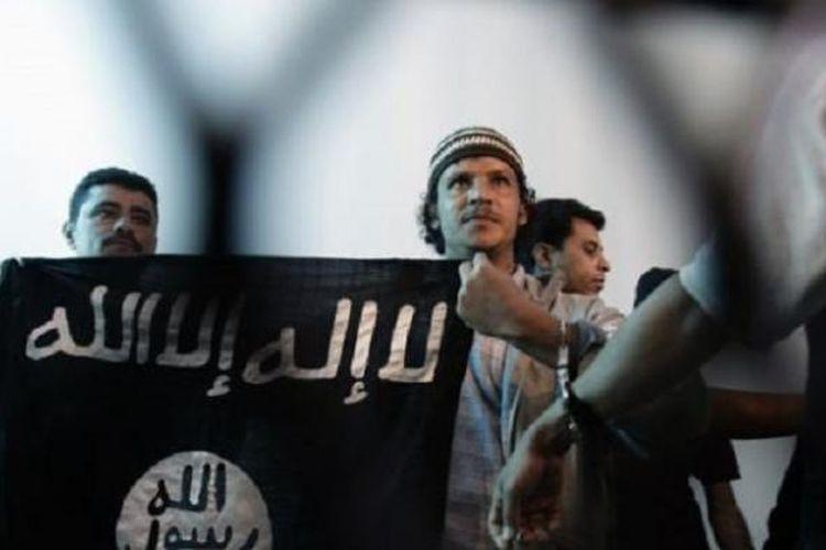 Dalam foto dokumentasi dari tahun 2013 ini, seorang yang diduga sebagai militan Al Qaeda di Yaman, tengah, membentangkan bendera kelompok ISIS di tengah berlangsungnya sebuah persidangan di Sana'a, Yaman. Dalam persaingannya dengan kelompok Negara Islam (ISIS) di Timur Tengah, Al Qaeda menggunakan pendekatan yang dianggap sebagian kalangan sebagai pragmatis.