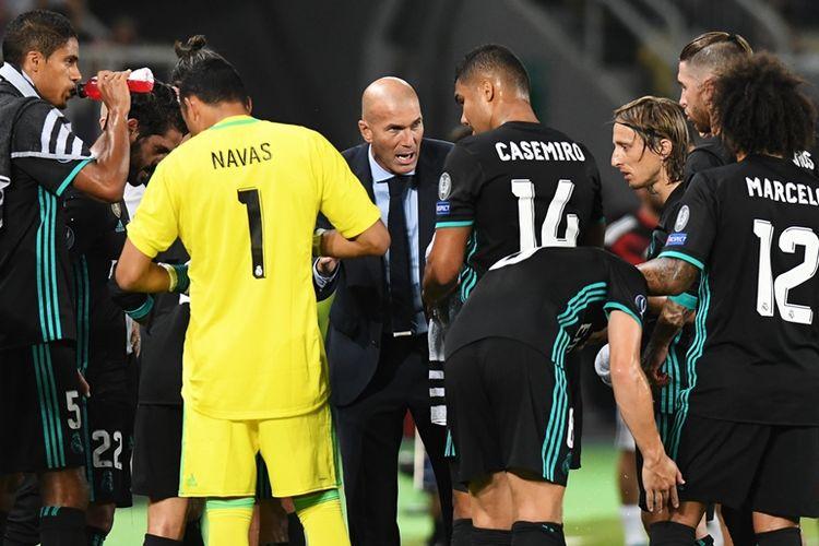 Pelatih Real Madrid, Zinedine Zidane (berdasi), memberikan instruksi kepada para pemain dalam pertandingan Piala Super Eropa melawan Manchester United di Philip II Arena, Skopje, Selasa (8/8/2017).