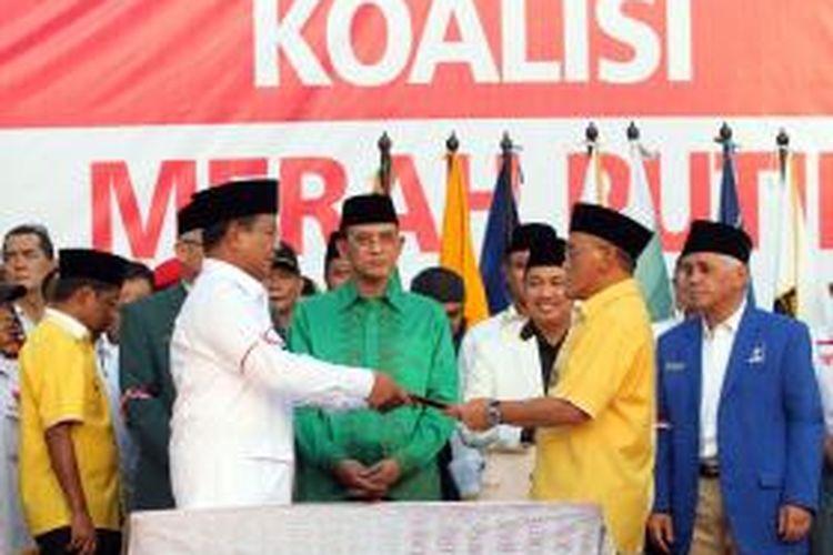 Ketua Umum Partai Golkar Aburizal Bakrie (kanan) mewakili ketua-ketua parpol pendukung menyerahkan piagam Koalisi Merah Putih Permanan kepada calon presiden nomor urut 1 Prabowo Subianto di Tugu Proklamasi, Jakarta Pusat, Senin (14/7/2014). Ketua dan Sekjen Partai Politik pendukung pasangan Prabowo-Hatta yaitu Gerindra, PKS, PPP, Golkar, PBB, PAN, dan Demokrat, untuk menguatkan komitmennya menandatangani nota kesepahaman Koalisi Permanen mendukung Prabowo-Hatta.