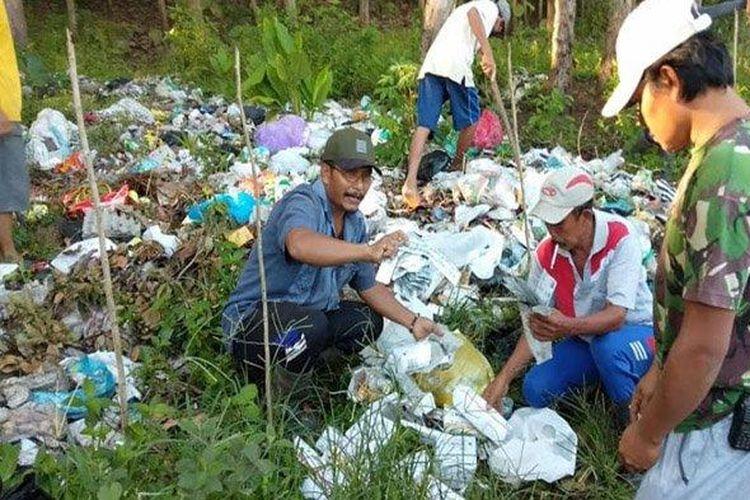 Warga dan petugas memeriksa ribuan sampah medis di lingkungan Gondanglegi, Kelurahan/Kecamatan Sutojayan,Kabupaten Blitar, Selasa (13/4/2021).