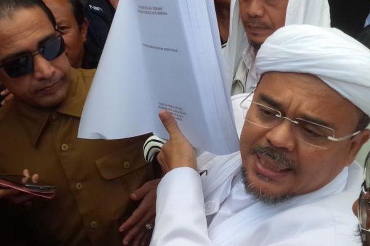 Pemimpin Front Pembela Islam Rizieq Shihab menunjukkan tesisnya sebelum diperiksa oleh penyidik Polda Jawa Barat, Senin (13//2/2017).
