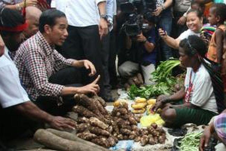 Joko Widodo (Jokowi) membeli keladi dari pedagang di Pasar Baru Sentani, Jayapura, Papua, Kamis (5/6/2014), saat kampanye Pilpres 2014.